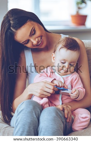 Best mom. Beautiful young woman holding baby girl with toy on her knees and looking at her with smile while sitting on the couch at home - stock photo