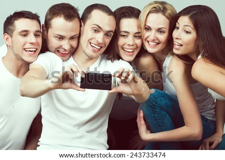 Best moments concept. Group of happy smiling and laughing friends in casual clothing taking selfie with smartphone. Urban street style. Studio shot