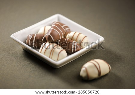 Best quality arabian dates coated with white and brown chocolate. Few chocolates in a small white plate. - stock photo