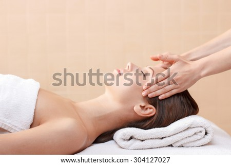 Best relaxation. Professional spa specialist making massage to charming young lady closing her eyes and lying on the couch.