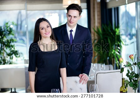Best romantic dinner in a restaurant. Young loving couple visits a restaurant. Woman standing near a man while the man sat down at the table and a woman looking directly into the camera - stock photo
