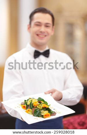 Best salads from our chef. Handsome waiter in uniform stretching out exquisite salad on the plate while serving customers in the luxury restaurant with selective focus - stock photo