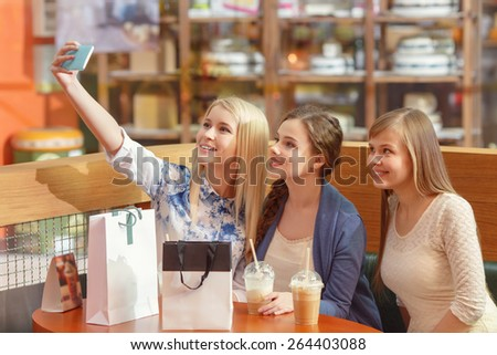 Best selfie for social media posting. Beautiful girls with shopping bags copy space taking a selfie with their cell phone - stock photo