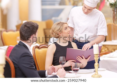 Best service in the town. Confident chef giving his recommendations to beautiful couple looking at menu while sitting in luxury restaurant  - stock photo