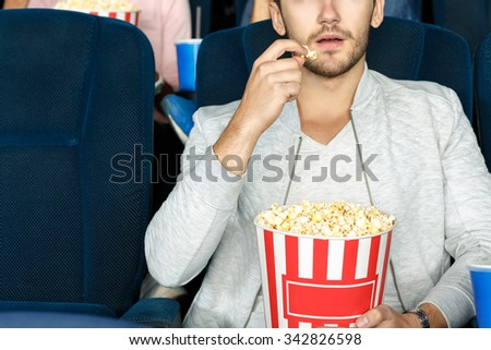 Best snack for cinema. Cropped shot of a man eating popcorn in a movie theater - stock photo