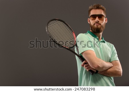 Best tennis player. Young sportsman holding tennis racket and his hands crossed on the chest while standing against grey background with copy space - stock photo