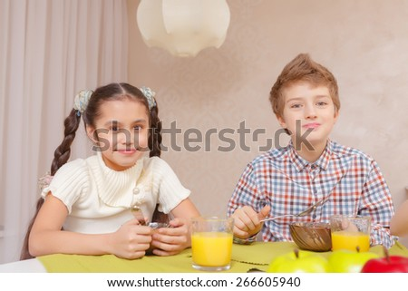 Best time for lunch. A schoolboy and a schoolgirl smiling at a camera while having lunch at home - stock photo