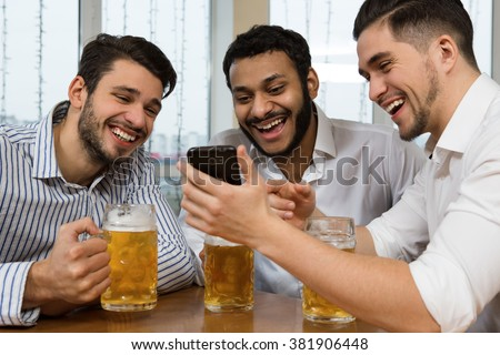 Best times with friends. Low angle shot of a cheerful businessman showing something in his phone to his friends laughing over drinks at the pub - stock photo