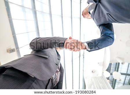 Best top deal! Two young businessman standing opposite each other and shake their hands.young people smiling into the camera. Close-up view from below - stock photo