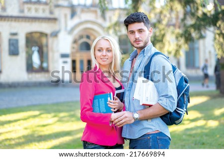Best university days. Couple of students standing together holding books looking at the camera while standing on the grass against the building of the university - stock photo