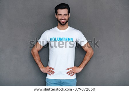 Best volunteer. Confident young man in volunteer t-shirt keeping hands on hips and looking at camera with smile while standing against grey background