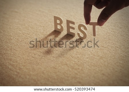 BEST wood word on compressed board with human's finger at T letter
