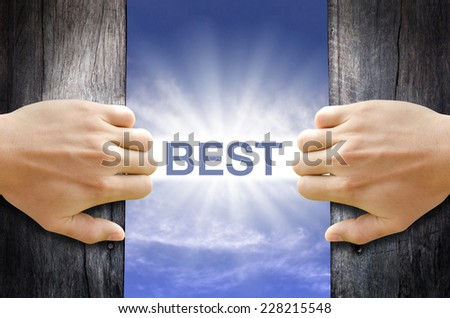 Best word floating and shining in the sky while two hands opening an old wooden door. - stock photo