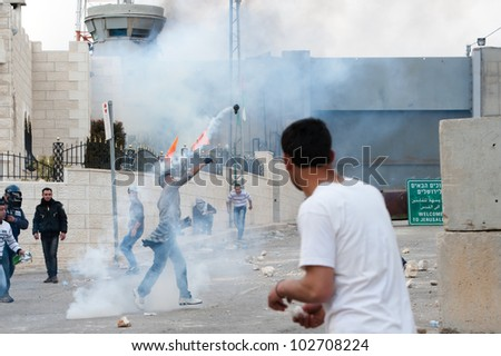 BETHLEHEM, PALESTINIAN TERRITORIES - MARCH 30: A Palestinian throws aside a tear gas grenade fired by Israeli soldiers during clashes at the Bethlehem checkpoint during protests on March 30, 2012. - stock photo
