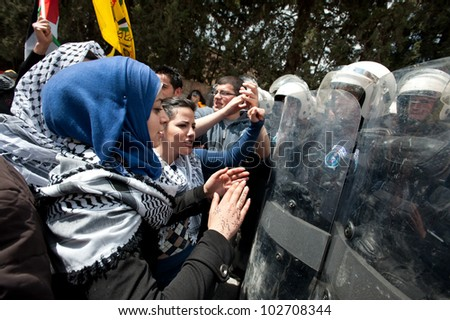 BETHLEHEM, PALESTINIAN TERRITORIES - MARCH 30: Palestinian women confront Palestinian Authority riot police blocking access to the Bethlehem checkpoint during Land Day protests on March 30, 2012. - stock photo