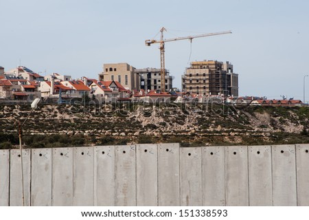 BETHLEHEM, PALESTINIAN TERRITORY - FEBRUARY 25: Construction continues in the Israeli settlement Gilo, seen over the Israeli separation wall surrounding Bethlehem, West Bank, February 25, 2013.