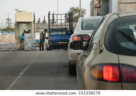 BETHLEHEM, PALESTINIAN TERRITORY - MARCH 3: A soldier checks cars passing through the Israeli military checkpoint controlling movement between Bethlehem and Jerusalem, March 3, 2013. - stock photo