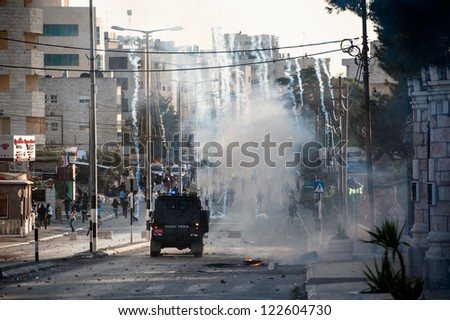 BETHLEHEM, PALESTINIAN TERRITORY - NOVEMBER 20: An Israeli military jeep launches tear gas in the West Bank town of Bethlehem during protests against Israel's attacks on Gaza, November 20, 2012. - stock photo