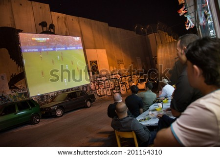 BETHLEHEM, WEST BANK - JUNE 18: Palestinians at a cafe watch a World Cup soccer game projected on the Israeli separation wall inside the West Bank town of Bethlehem, June 18, 2014. - stock photo