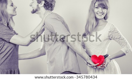 Betrayal and infidelity concept. Handsome boy with two attractive blondie girls. Man cheating women by mislead chosen one and offer his heart to another. Selective color - stock photo