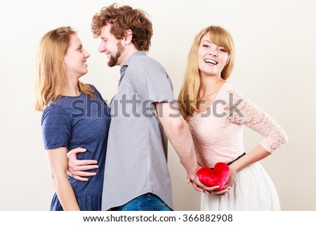 Betrayal and infidelity concept. Handsome boy with two attractive blondie girls. Man cheating women by mislead chosen one and offer his heart to another. - stock photo