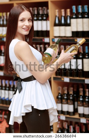 Better take both. Portrait of an attractive young woman holding two wine bottles copyspace near the shelves of the store and smiling at a camera - stock photo
