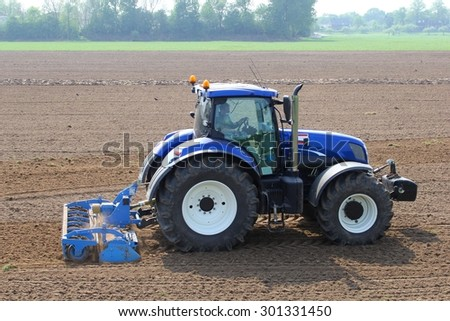 Betuwe, Netherlands, 25 april 2014, A tractor is plowing the agricultural fields in the village Tricht, municipality Geldermalsen - stock photo