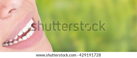 Beuatiful woman smile with perfect teeth in close-up against green background with copy space - stock photo