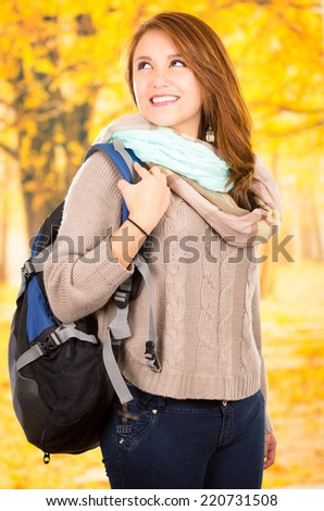 Beuatiful young happy female student going back to school on fall - stock photo