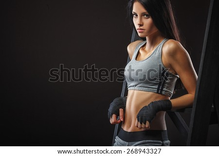 beutiful brunette woman boxer standing near ladder over dark background closeup view