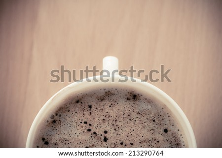 Beverage. Closeup of cup of hot drink coffee cappuccino with froth on wooden table background. - stock photo
