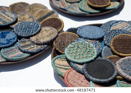 Beverage mats in various colors made from carpet sections are laid out to dry on trays at an outdoor bar - stock photo