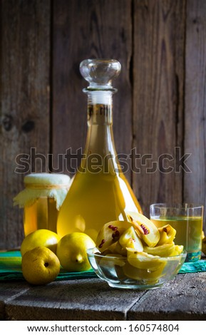 Beverage of quince and fruit on a wooden table - stock photo