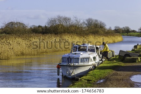 BEVERLEY, UK - FEBRUARY 02: A man unloads goods from a small boat on the river Hull on a fine winter's morning on February 02, 2014 near Beverley, Yorkshire, UK.