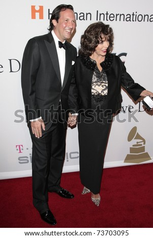 BEVERLY HILLS - FEB 7:  Joan Collins and husband Percy Gibson arriving at the Clive Davis and The Recording Academy present the Annual Pre-Grammy Gala in Beverly Hills, California on February 7, 2009. - stock photo