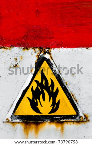 Beware of fire sign on rusty metal - stock photo