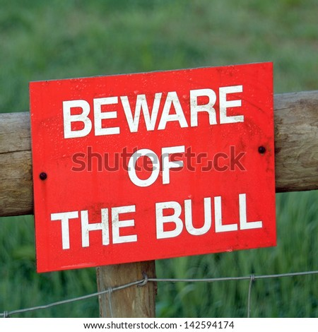 Beware of the bull warning sign on farm gate England United Kingdom - stock photo