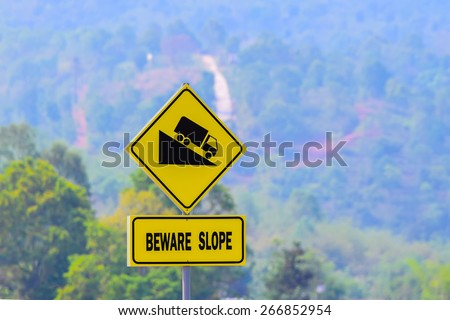 Beware slope Sign, with blurred uphill road. - stock photo