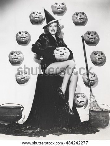 Bewitching woman sitting among carved pumpkins