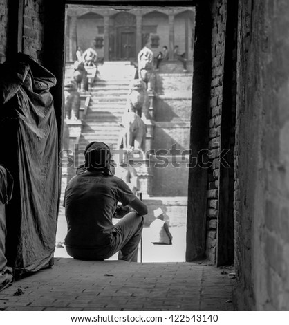 Bhaktapur - Nepal 2015 - A man cools off  on the door way on a sunny day.