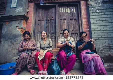 BHAKTAPUR, NEPAL, APRIL 25: A group of women in Bhaktapur smiling and working in the street. Bhaktapur is one of 3 Royal cities in the Kathmandu Valley in Nepal and considered a cultural gem. 2013. - stock photo