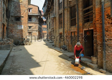 BHAKTAPUR, NEPAL - APRIL 20, 2016: hindu old woman washing pots in a beautiful street of medieval town of Bhaktapur in Nepal.