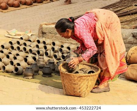 BHAKTAPUR, NEPAL, APRIL 03: Nepali woman dries the clay vases. Bhaktapur, Nepal on April 03, 2014 - stock photo