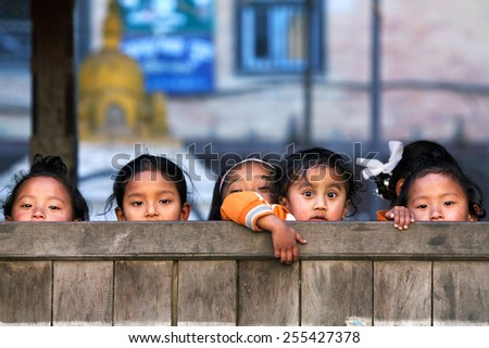 BHAKTAPUR, NEPAL - JANUARY 8: Nepalese schoolgirls poses for a photo during their break time on January 8, 2010 in Bhaktapur, Kathmandu Valley, Nepal. - stock photo
