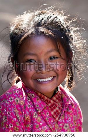 BHAKTAPUR, NEPAL - JANUARY 08: Nevaris schoolgirl Lakshmi, 8, poses for a photo during her breaktime on January 08, 2010 in Bhaktapur, Kathmandu Valley, Nepal. - stock photo