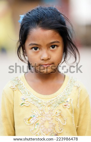 BHAKTAPUR, NEPAL, NOVEMBER 24, 2010: Portrait of a Nepalese little girl posing in the main Bhaktapur square - stock photo