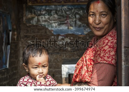 BHAKTAPUR, NEPAL - SEPTEMBER 31, 2013: An undefined napalese woman and a child portrayed in NEPAL - stock photo