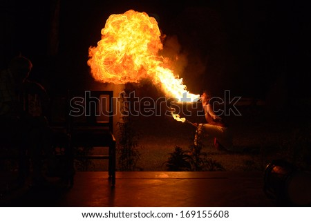 BHATATPUR, INDIA - CIRCA OCTOBER: Fire breather perform in outdoor in Bharatpur, India. Night time, high iso. The silhouette of one person and empty chair on left.