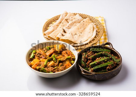 bhindi masala or bhendi masala or ladies finger fry with mixed veg in red curry with indian roti / chapati / fulka / paratha / indian bread, indian spicy food - stock photo
