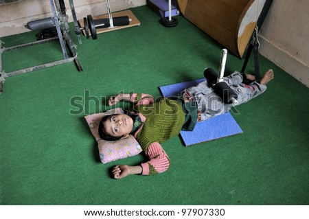 BHOPAL- NOVEMBER 23:  10 years old Razip who is suffering from spastic cerebral palsy getting treatment in a free clinic in Bhopal - India on November 23, 2010. - stock photo